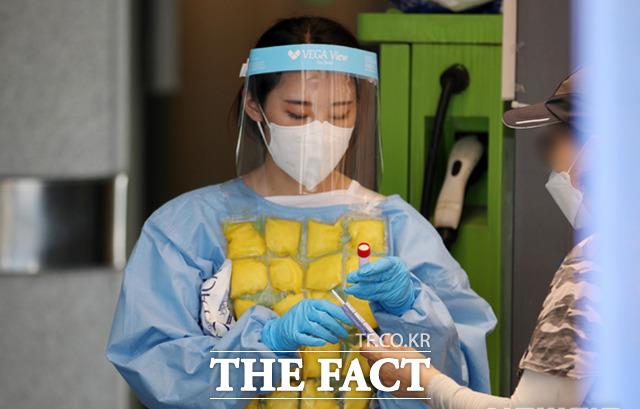 27일 오전 서울 동작구 보건소 선별진료소에서 의료진이 얼음 조끼를 입고 검사를 받으러 온 시민들을 안내하고 있다. /뉴시스