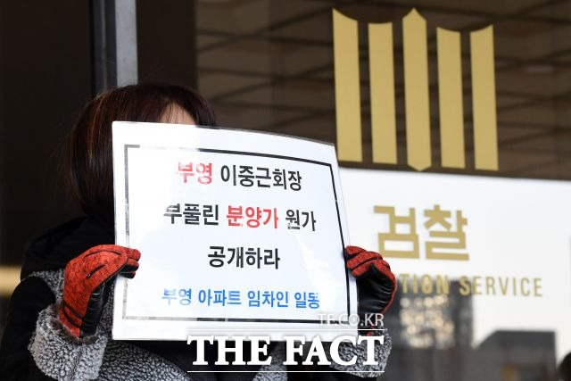 이중근 회장이 불출석한 검찰청사 앞에 부영 아파트 임차인 피해자가 피켓을 들고 있다. /남윤호 기자