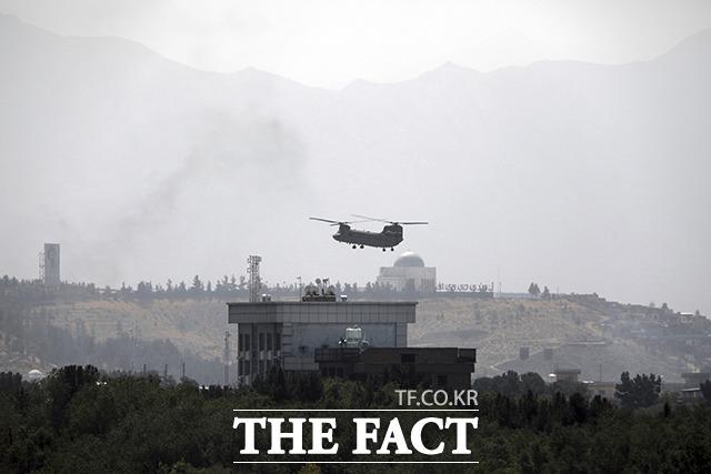 이슬람 무장단체 탈레반이 아프가니스탄 카불에 진입한 15일(현지시간) 인력 철수에 나선 미군의 치누크 헬기가 카불 주재 미 대사관 상공을 비행하고 있다. /카불=AP.뉴시스