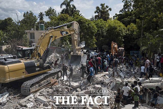 무너진 건물의 잔해를 치우는 모습과