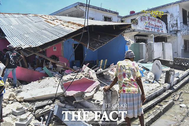 아이티에 규모 7.2의 강진이 발생한 14일(현지시간) 아이티 레카이의 한 주민이 무너진 집 앞에 망연자실하게 서 있다. /레카이=AP.뉴시스
