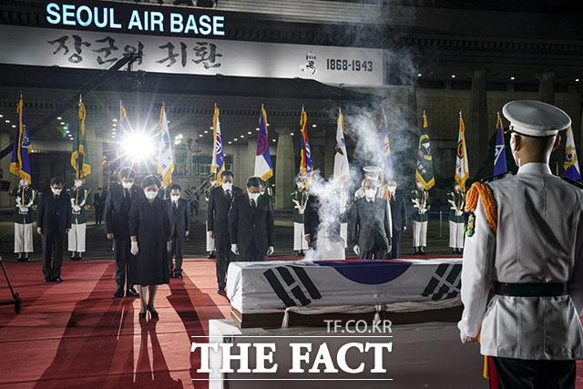 문재인 대통령이 15일 서울공항에서 거행된 '홍범도 장군 유해 봉환식'에서 김정숙 여사를 비롯한 주요 내빈들과 함께 묵념을 하고 있다.