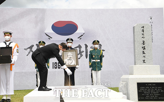 카자흐스탄 홍범도 장군 묘역의 흙과 대한민국의 흙을 허토하는 문 대통령.