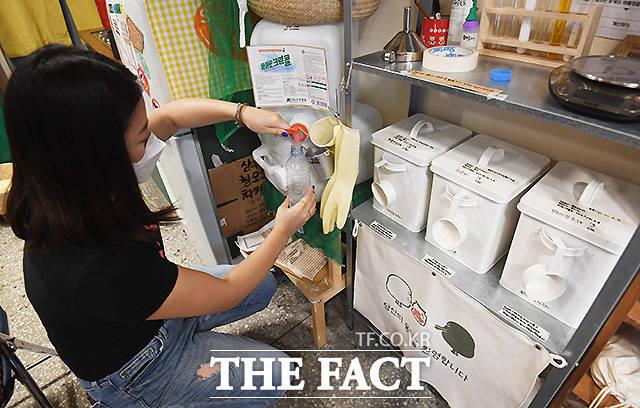 순환지구를 찾은 한 소비자가 빈 용기에 액체 세제를 담고 있다.
