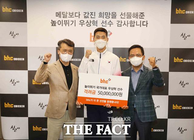 박현종 회장과 우상혁 선수, 임금옥 대표(왼쪽부터)가 격려금을 전달하며 기념사진을 찍고 있다.