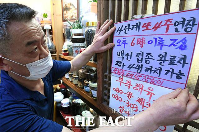 6일 오후 서울 종로구 광화문의 한 음식점에서 관계자가 거리두기 연장과 백신 인센티브 관련 문구가 적힌 안내문을 붙이고 있다. /남용희 기자