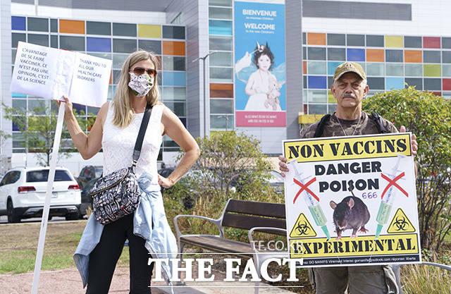 13일(현지시간) 캐나다 몬트리올의 한 병원 앞에서 코로나19 백신 찬·반 시위대가 각각 손피켓을 들고 1인 시위를 벌이고 있다. /몬트리올=AP.뉴시스
