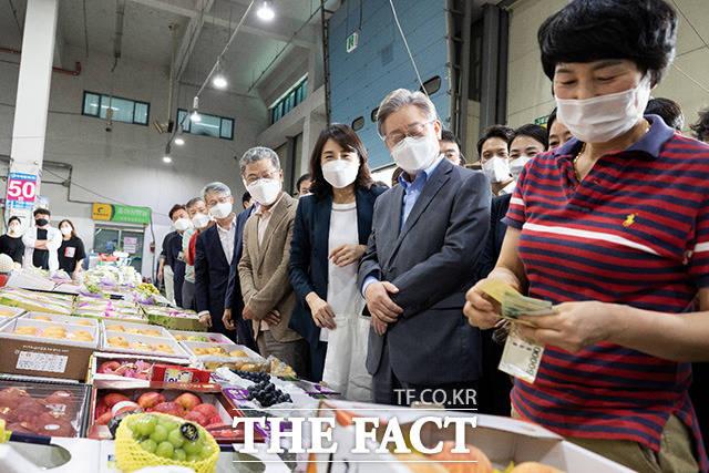 더불어민주당 대선 예비후보인 이재명 경기도지사(오른쪽 두번째)와 아내 김혜경 씨가 18일 광주광역시 서부 농수산물 도매시장을 방문해 상인들과 인사를 나누고 있다./이재명 캠프 제공