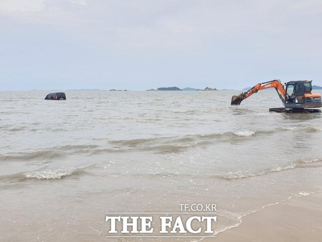 주민들이 동원한 굴삭기가 차량을 꺼내기 위해 바다로 향하고 있다. / 독자 제공
