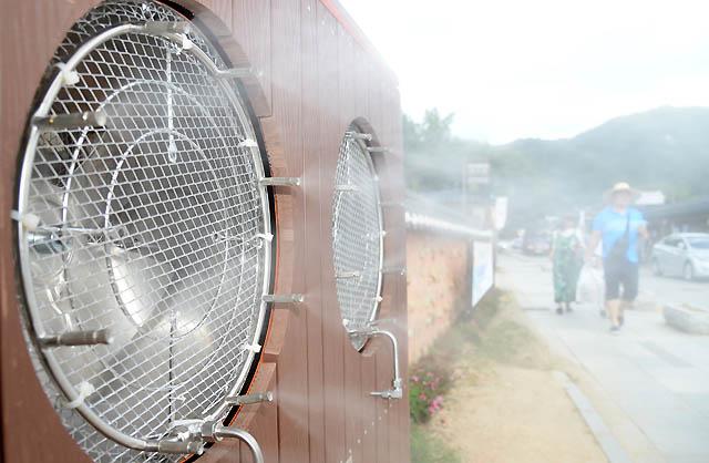 폭염이 지속되는 31일 전북 전주 한옥마을에 시민들과 관광객들의 더위를 날려줄 쿨링 포그(Cooling Fog)가 설치된 가운데 한옥마을 향교길을 지나는 시민들이 시원한 물바람을 맞고 있다. 전주 한옥마을 쿨링 포그(Cooling Fog)는 오전 11시부터 오후 6시까지 가동되며 30분 가동 후 5분 휴식을 거치며 운행된다./전주=뉴시스