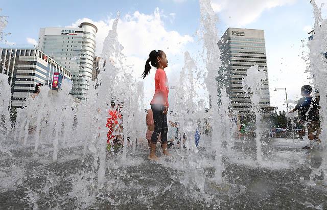 서울과 전국 대부분 지역에 폭염경보가 이어지고 있는 31일 오후 서울 종로구 광화문광장 분수대에서 어린이들이 물놀이를 즐기며 더위를 피하고 있다. /서울=뉴시스