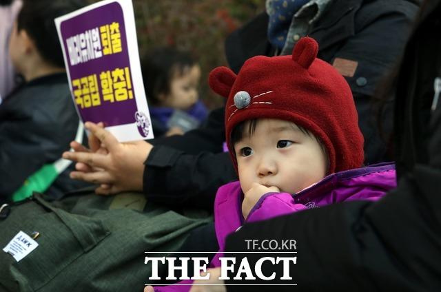 학생들은 부모를 위한 교육이 필요하다고 강조했다. 지난 10월 서울 시청역 앞에서 열린 유아교육, 보육 정상화를 위한 모두의 집회에서 한 어린이가 엄마 무릎에 앉아 간식을 먹고 있는 모습. /뉴시스