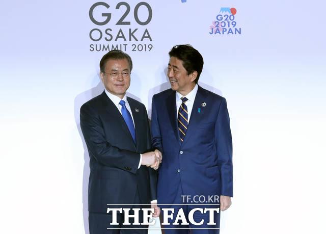 문재인 대통령이 지난해 6월 G20 정상회의 공식환영식에서 아베 신조 일본 총리와 악수하고 있다. 일본 정부가 독도 영유권을 주장하는 외교 청서를 발간한 다음날 방위상 집무실에 한반도기를 걸고 소셜미디어에 게재해 논란이 되고 있다. /뉴시스