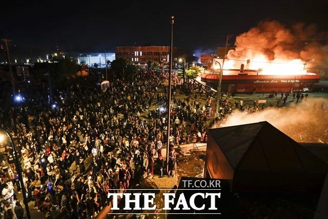 미국 미네소타주 미네아폴리스에서 29일(현지시간) 불타고 있는 경찰서 앞에서 백인 경찰의 비무장 흑인 남성 살해 사건에 항의하는 시위가 벌어지고 있다. /AP·뉴시스