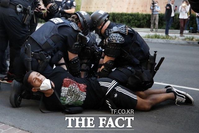 트럼프 대통령의 이러한 강경대응의 배경으론 공화당 지지층 결집으로 꼽힌다. 1일(현지시간) 미 워싱턴DC 백악관 인근에서 조지 플로이드 사망에 대한 시위가 이어진 가운데 통행금지 발효 후 한 시위 남성이 경찰에 연행되고 있다/AP.뉴시스