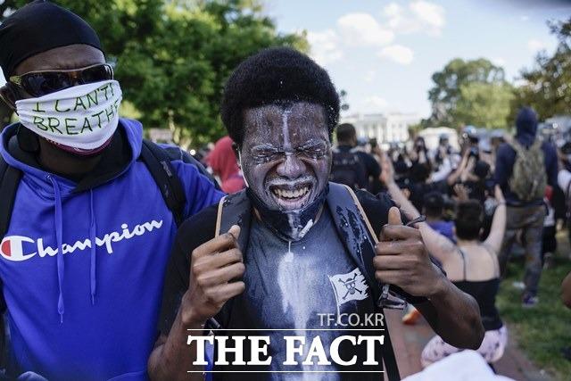 트럼프 대통령이 강경 진압을 발표한 이날에도 시위대가 다시 백악관 앞으로 몰려 경찰은 최루탄과 고무탄을 발사하기도 했다. 5월 31일(현지시간) 미 워싱턴DC 백악관 근처에서 플로이드의 죽음에 항의하는 시위 도중 한 남성이 최루 가스를 씻어내기 위해 우유로 눈을 씻어내고 있다. /AP.뉴시스