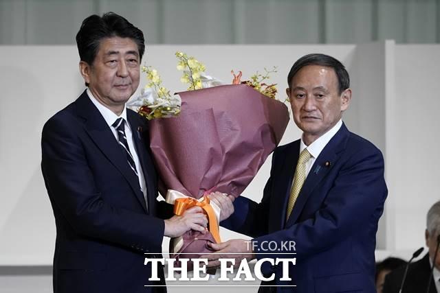 스가(오른쪽) 관방장관이 사실상 새 총리로 확정돼 한일관계에 미칠 영향에 관심이 쏠리고 있다. 아베 신조 일본 총리가 14일 도쿄의 한 호텔에서 열린 자민당 총재 선거에서 총재로 선출된 스가 요시히데 관방장관에게 꽃다발을 건네며 축하하는 모습. /AP.뉴시스