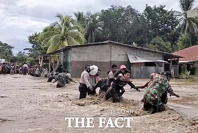 인도네시아와 동티모르 일대에 홍수와 산사태가 발생해 이재민이 속출하고 있는 가운데 5일(현지시간) 인도네시아 동부지역에서 군인들이 주민들을 구조하고 있다. /인도네시아=AP,뉴시스