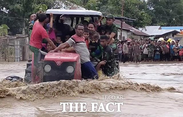 인도네시아 군인들이 홍수로 범람 된 도로에서 트랙터를 이용해 주민들을 구조하고 있다.