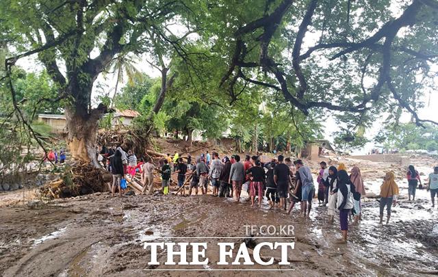 인도네시아 동부 플로레스 아도 나라 섬의 한 마을이 홍수로 인해 다리가 유실된 가운데 강을 건너기 위해 사람들이 줄을 서있다.