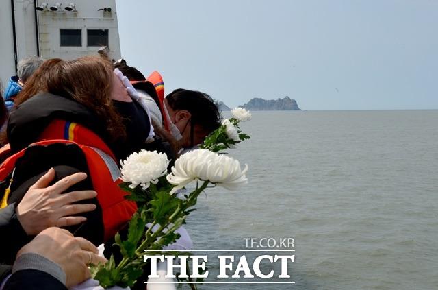 세월호 참사 7주기인 16일 오전 희생자 가족들이 전남 진도군 동거차도 인근 사고 해역을 찾아 바다를 향해 국화를 던지고 있다. /뉴시스